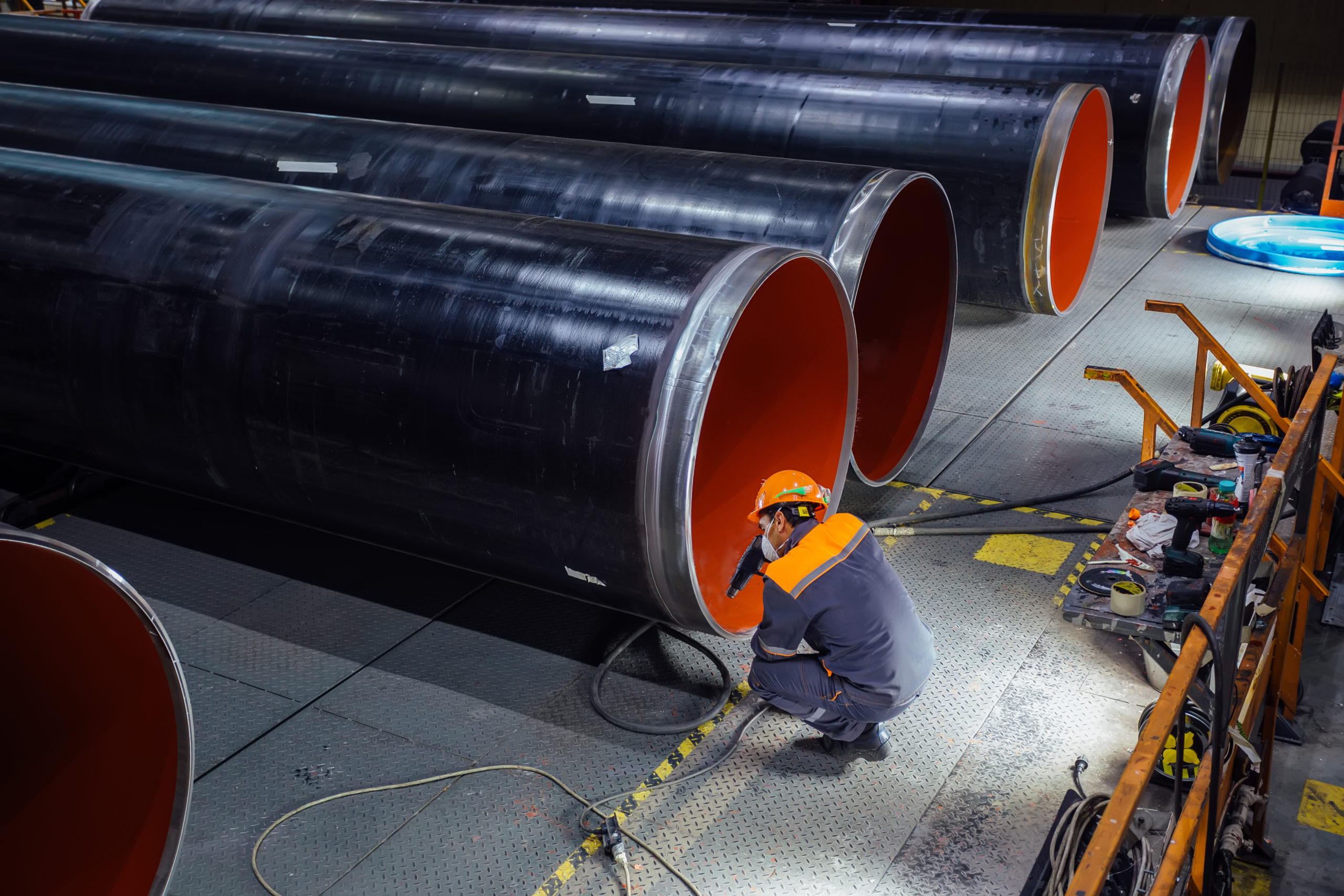 Worker,Examines,New,Coated,Pipe,In,Factory.